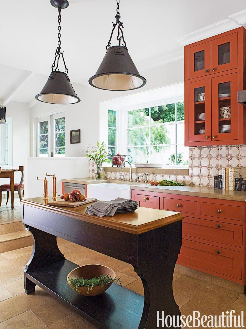 "<p>Burnt orange cabinets are unexpected, but add a rustic touch to a kitchen. To add to the effect, hand-forged iron lanterns were hung, but painted white inside to reflect more light onto the <a href=""https://www.housebeautiful.com/room-decorating/kitchens/g1857/burnt-orange-kitchen-0514/"" rel=""nofollow noopener"" target=""_blank"" data-ylk=""slk:island"" class=""link rapid-noclick-resp"">island</a>. Copy this slim kitchen island if your space is small since it gets the job done without looking out of scale. </p>"