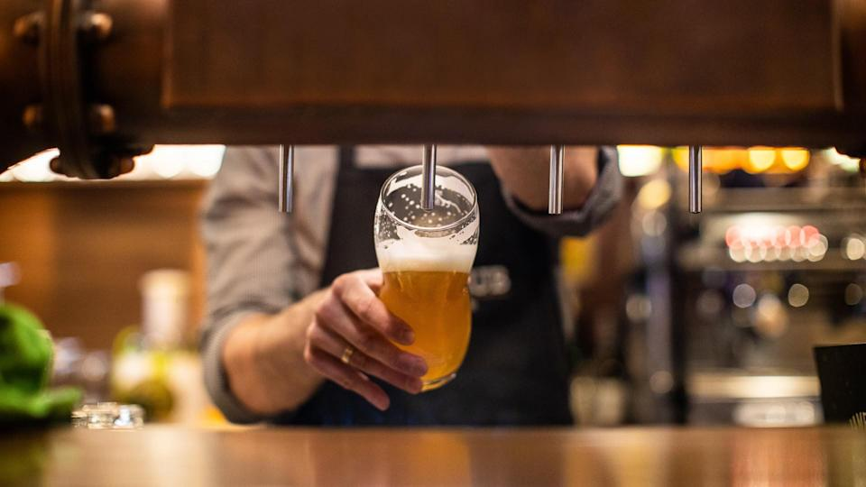 Unrecognizable man pouring a beer on beer tap in drinking glass, in a pub.