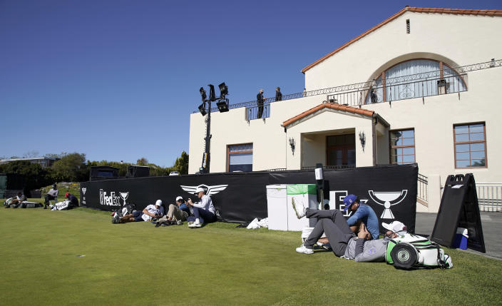 Players and caddies lounge on the practice green after high winds suspended play during the third round of the Genesis Invitational golf tournament at Riviera Country Club, Saturday, Feb. 20, 2021, in the Pacific Palisades area of Los Angeles. (AP Photo/Ryan Kang)