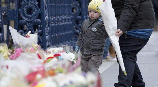 A young boy arrives with flowers for victims of Monday's refuse truck accident in Glasgow. Photo: AFP