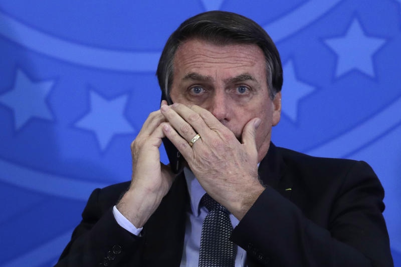 Brazil's President Jair Bolsonaro talks on his cell phone during a ceremony at Planalto presidential palace, in Brasilia, Brazil, Tuesday, July 23, 2019. (AP Photo/Eraldo Peres)