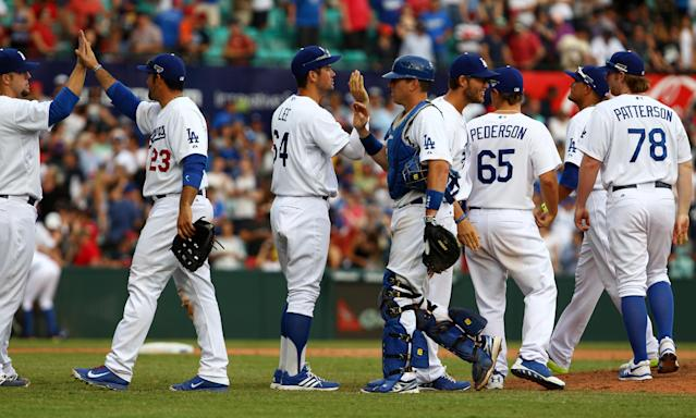 Los Angeles Dodgers' teammates congratulate each other after defeating the Diamondbacks during the second game of the two-game Major League Baseball opening series between the Los Angeles Dodgers and Arizona Diamondbacks at the Sydney Cricket ground in Sydney, Sunday, March 23, 2014. The Dodgers won the game 7-5 and the series 2-0. (AP Photo/Michelle O'Connor)