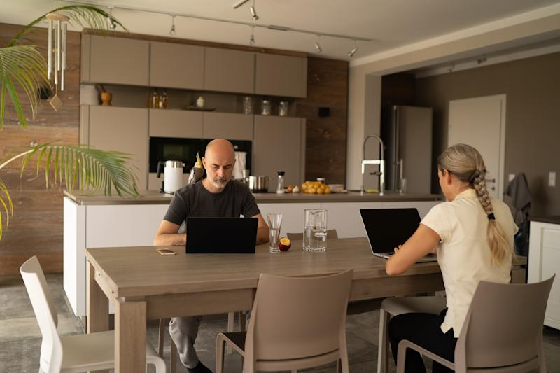 mature adult european couple sitting together at wooden table at home in their modern house in austria working in homeoffice during coronavirus crisis