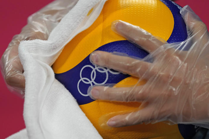 FILE - In this July 23, 2021, file photo, a steward uses a plastic glove and a cloth to disinfect a volleyball during a rehearsal for the start of the volleyball preliminaries at Ariake Arena during the 2020 Summer Olympics in Tokyo, Japan. (AP Photo/Frank Augstein, File)