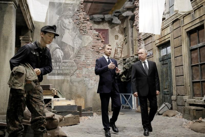 Russian President Vladimir Putin, right, examines an exhibition depicting a Berlin street after surrender in 1945 at 3D panorama 'Memory speaks. The road through the war' in St.Petersburg