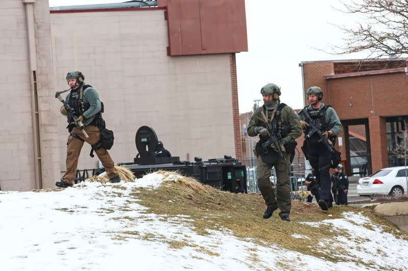Law enforcement officers sweep the area outside of a King Supers grocery store, which was the site of a shooting in Boulder