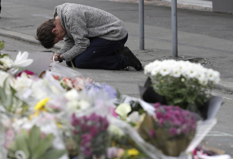 """FILE - In this Tuesday, March 19, 2019, file photo, a mourner prays near the Linwood mosque in Christchurch, New Zealand. New Zealand Prime Minister Jacinda Ardern was hailed around the world for her decisive response to the two mosque shootings by a white nationalist who killed 50 worshippers. For many Muslims, her most consequential move was immediately labeling the attack an act of terrorism. Community leaders and researchers say that for too long, terrorism was considered a """"Muslim problem"""" and that a double standard persists when attacker is white and non-Muslim. (AP Photo/Mark Baker, File)"""