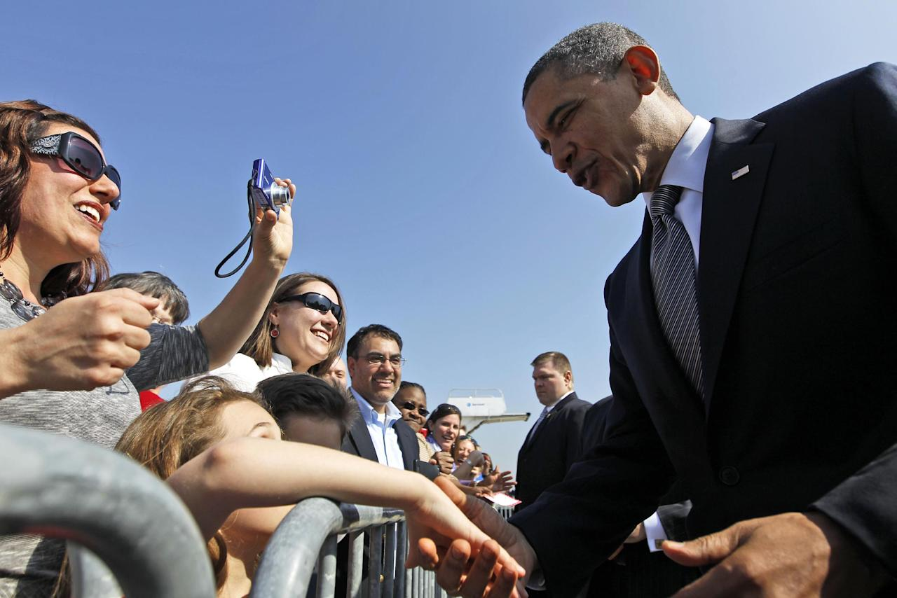 President Barack Obama greets supporters on the tarmac on his arrival at O'Hare International Airport in Chicago, Friday, March, 16, 2012. (AP Photo/Pablo Martinez Monsivais)