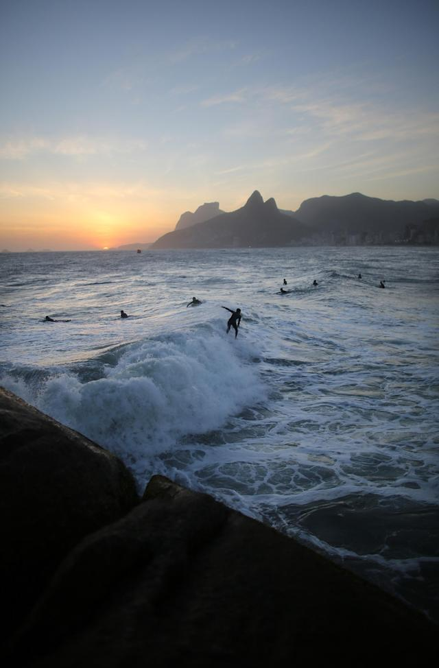 RIO DE JANEIRO, BRAZIL - NOVEMBER 02: People surf at sunset at Ipanema Beach on the Day of the Dead on November 2, 2013 in Rio de Janeiro, Brazil. Brazilians often mark the traditional Latin American holiday by visiting loved ones' graves while the Zombie Walk on nearby Copacabana Beach offered a modern twist. (Photo by Mario Tama/Getty Images)