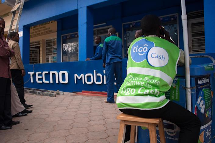 Workers prepare to hoist a Tecno Mobile sign above a new phone store in Kigali, Rwanda. (Photo: Will Boase/Bloomberg via Getty Images)