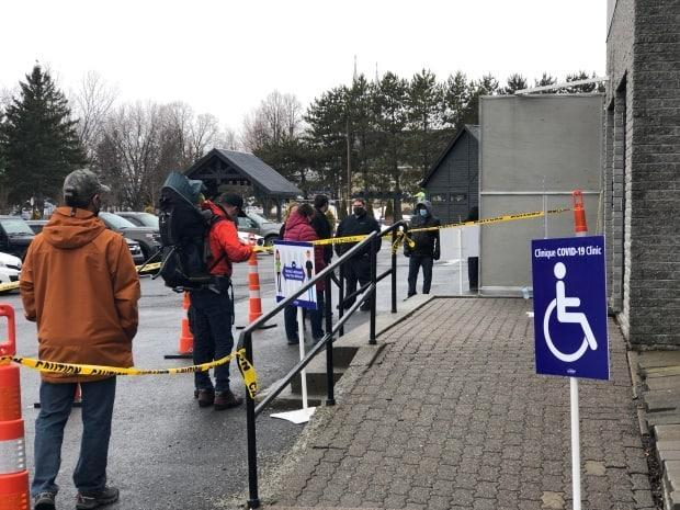 Residents line up at a mass testing clinic Thursday in Edmundston, which is currently seeing a surge of cases. The clinics, for asymptomatic residents only, will run Thursday and Friday. (Gary Moore/CBC News - image credit)