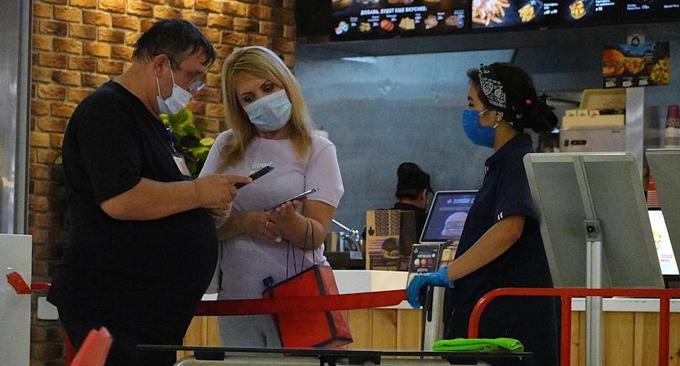 People in masks at food court in Russia.