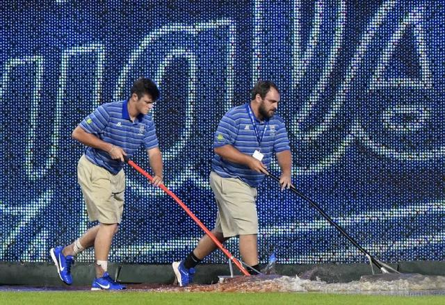 Members of the Royals' grounds crew work to clear water from the field after water pipe broke at Kauffman Stadium. (Getty Images)