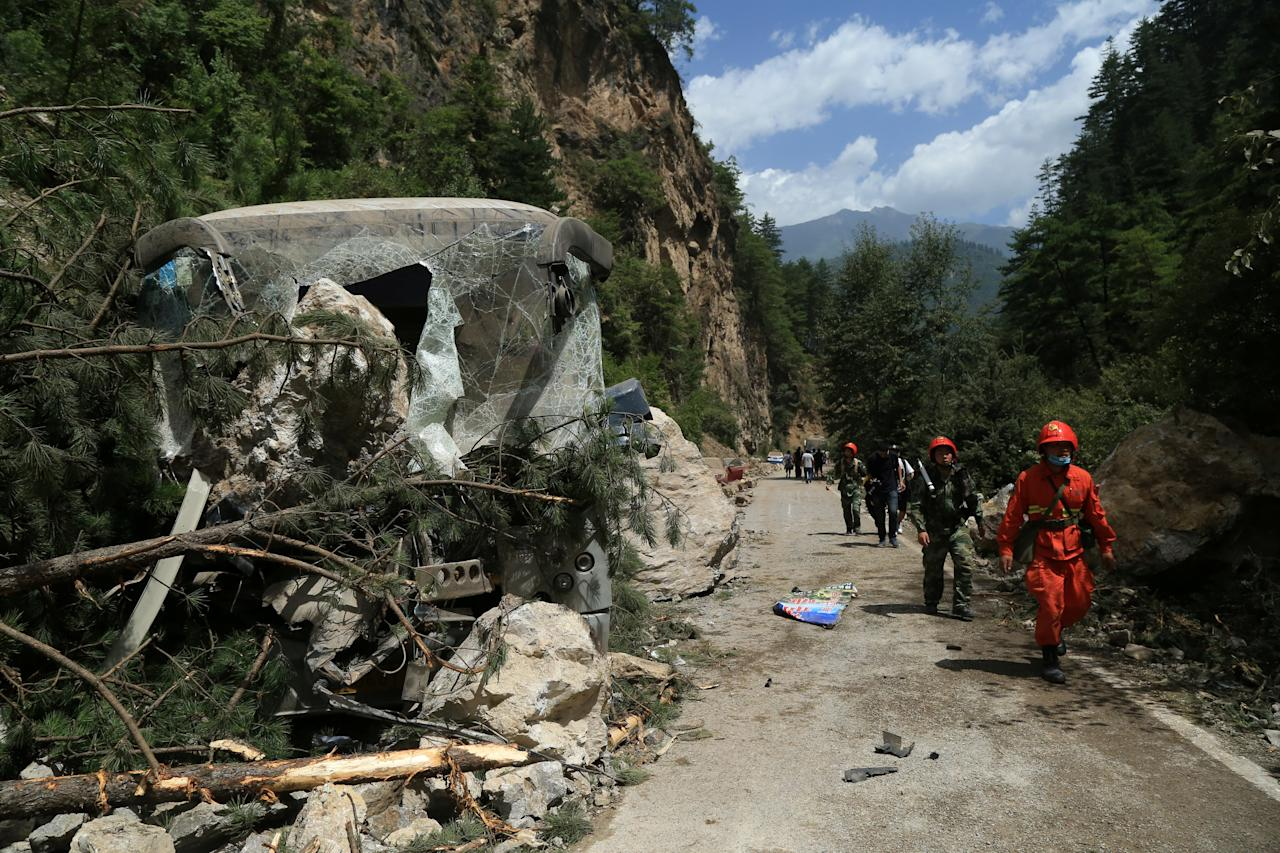 <p>Rescue workers walk past a collapsed area after an earthquake in Jiuzhaigou county, Ngawa prefecture, Sichuan province, China, Aug. 9, 2017. (Photo: Stringer/Reuters) </p>