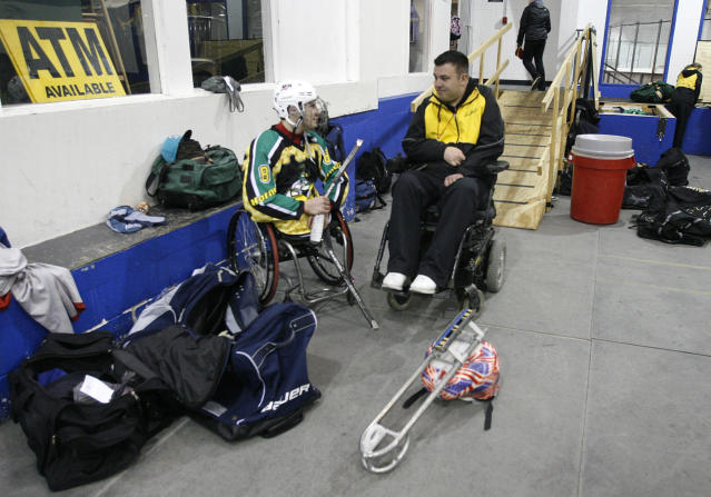 "Brody Roybal, 15, left, talks with J.J. O'Connor, the general manager of the Hornets youth sled hockey team during a team practice on Tuesday, Feb. 11, 2014, in Addison, Ill. O'Connor, who lost use of his arms and legs after a hockey accident when he was a teen, said he feels like he's living vicariously through Roybal. ""Everybody dreams of representing their country and being an Olympian and winning a gold medal,"" O'Connor says. ""That's something that I wasn't able to do. And this is the next best thing."" (AP Photo/Martha Irvine)"