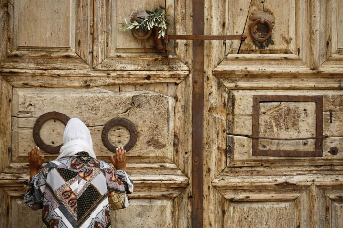 A woman prays in front of the closed Church of the Holy Sepulchre, a place where Christians believe Jesus Christ was buried, as a palm hangs on the door, in Jerusalem's Old City, Sunday, April 5, 2020. The traditional Palm Sunday procession was cancelled due to restrictions imposed to contain the spread of the coronavirus. (AP Photo/Ariel Schalia