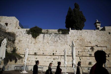 Tourists walk by part of the Western Wall, following the Israeli government's approval to create a mixed-sex prayer plaza near Jerusalem's Western Wall to accommodate Jews who contest Orthodox curbs on worship by women at the site, in Jerusalem's Old City January 31, 2016. REUTERS/Amir Cohen