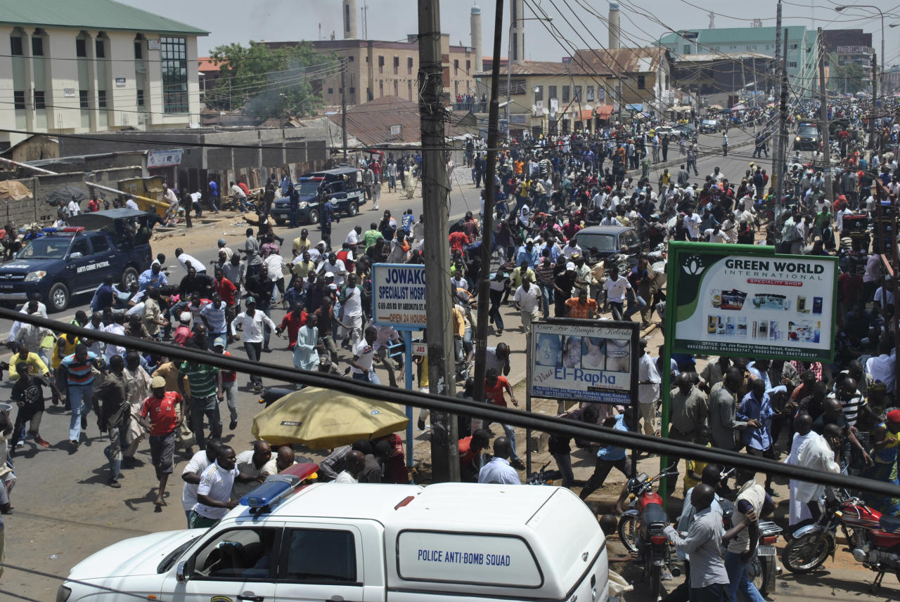 People gather at the site of a bomb explosion in Kaduna, Nigeria, Thursday, April. 26, 2012, A suicide bomber detonated a car loaded with explosives Thursday at the office of a major Nigerian newspaper in the country's capital and another man threw a bomb near another newspaper office in Kaduna, killing at least six people in the attacks, witnesses said. (AP Photos/Junaid Garba)