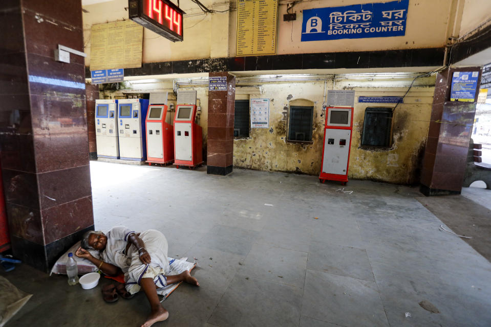 A homeless woman sleeps in front of closed ticket counters as local trains were suspended due to the coronavirus pandemic, at a local railway station in Kolkata, India, Saturday, Oct. 10, 2020. India's total coronavirus positive cases near 7 million with another 73,272 infections reported in the past 24 hours. The Health Ministry on Saturday put the total positive caseload at 6.97 million, second to 7.66 million infections registered in the worst-hit United States. (AP Photo/Bikas Das)