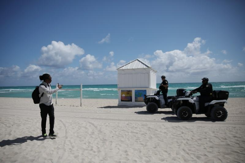 Police officers ask a man to leave after local authorities order the closing of all the beaches in Miami-Dade county for precaution due to coronavirus disease (COVID-19) spread, in Miami Beach, Florida, U.S.