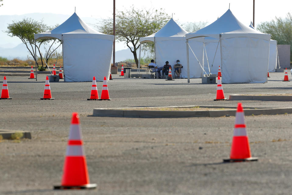 Health officials sit waiting for people to arrive to be tested for the COVID-19 Coronavirus Tuesday, July 28, 2020 at South Mountain Park in Phoenix. It was the last day of a 12-day blitz aimed at bringing tens of thousands of COVID-19 tests to underserved Latino communities in Phoenix but only 14,000 of some 55,000 tests were administered at the park and the western neighborhood of Maryvale, leaving more than 40,000 COVID-19 test kits unused. (AP Photo/Matt York)