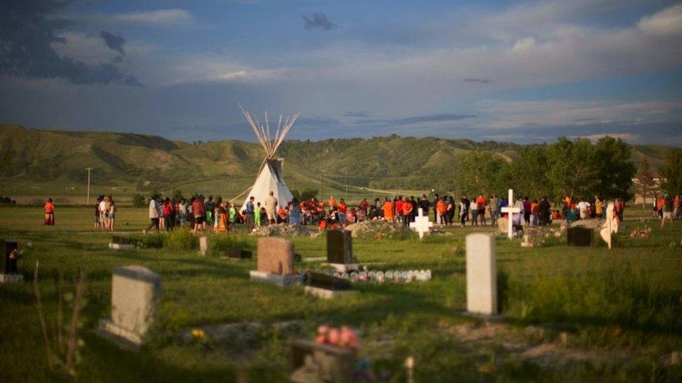 Hundreds of people gather for a vigil in a field where human remains were discovered in unmarked graves at the site of the former Marieval Indian Residential School on the Cowessess First Nation in Saskatchewan on June 26, 2021.
