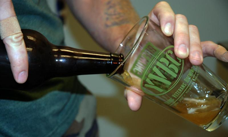 """In a Wednesday, Aug. 14, 2013, photo, Young Veterans Brewing Co. president and Iraq War veteran Thomas Wilder pours a glass of """"Jet Noise IPA,"""" at the Virginia Beach, Va., brewery. The brewery set to open in September in military-heavy Hampton Roads is part of a growing number of craft breweries popping up throughout Virginia and the country. Virginia, which is celebrating its second craft beer month in August, has seen the industry grow from about 40 craft breweries last year to more than 60 in 2013, with countless more in the works."""