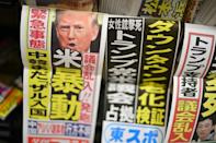 "A Japanese newspaper on sale at a convenience store in Tokyo has a headline reading ""US riot"""