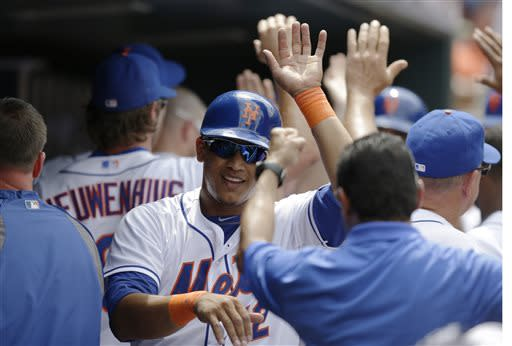 New York Mets' Juan Lagares, center, celebrates with teammates, coaches and trainers after umpires ruled his hit a fourth-inning three-run home run off Philadelphia Phillies starting pitcher Cliff Lee during a baseball game on Sunday, July 21, 2013, in New York. (AP Photo/Kathy Willens)