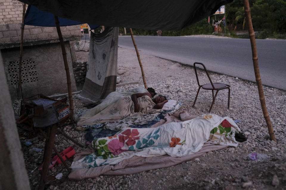 """Nurse Gabrielle Lagrenade, center, sleeps next to her daughter on the the side of the road in Les Cayes, Haiti, Monday, Aug. 23, 2021, nine days after a 7.2 magnitude earthquake made her rental home unsafe to live in. Lagrenade, 52, describes her current living conditions simply as """"inappropriate,"""" but she continues arriving for her daily shift at the hospital. (AP Photo/Matias Delacroix)"""