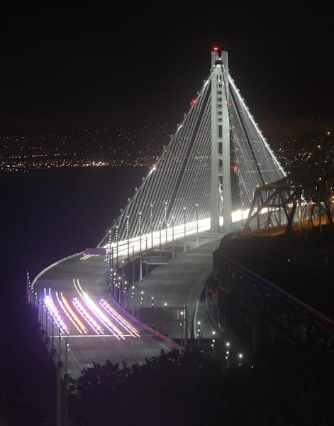 In this Monday, Sept. 2, 2013 photo taken in a long exposure and provided by the Bay Area Toll Authority, police vehicles open the San Francisco-Oakland Bay Bridge to traffic, in San Francisco. At the modest inaugural ceremony, the new, self-anchored suspension bridge with its single white tower was praised as a dramatic safety upgrade over its predecessor and a beautiful example of public art. (AP Photo/Bay Area Toll Authority, Noah Berger) MAGS OUT, NO SALES