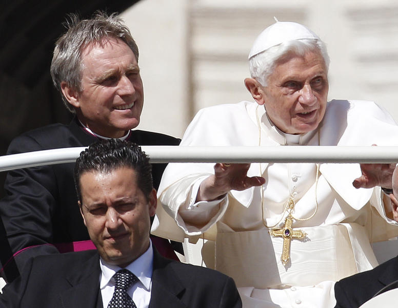 """FILE - In this file photo taken Wednesday, May 2, 2012, Pope Benedict XVI arrives in St. Peter's square at the Vatican for a general audience as his then-butler Paolo Gabriele, bottom, and his personal secretary Georg Gaenswein sit in the car with him. Pope Benedict XVI's ex-butler Paolo Gabriele and another Vatican lay employee, Claudio Sciarpelletti, are scheduled to go on trial Saturday, Sept. 29, 2012, in the embarrassing theft of papal documents that exposed alleged corruption at the Holy See's highest levels. Gabriele was arrested May 24 after Vatican police found what prosecutors called an """"enormous'' stash of documents from the pope's desk in his Vatican City apartment. (AP Photo/Alessandra Tarantino, File)"""