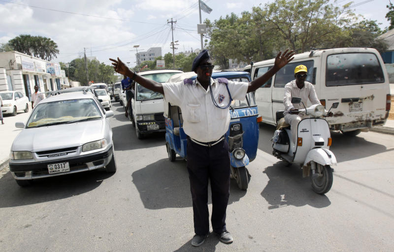 In this photo dated Sunday, Dec. 8, 2013, A Somali traffic police officer stands at a Mogadishu junction in a vain effort to regulate cars and traffic movements in Mogadishu, Somalia. The traffic police officer yells, waves his arms and blows his whistle for car drivers to obey the traffic signals but many don't notice the signals. Many of the cars do not stop, and angered, the police officer steps into the middle of the road, as other cars encroach further, obstructing another lane of traffic and creating a scene of gridlock and the unarmed officer is forced to allow more cars to run the red light in order to clear the congestion. (AP Photo/Farah Abdi Warsameh)