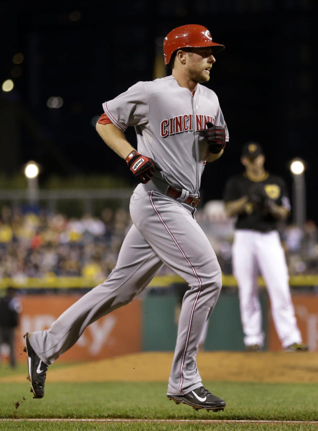 Cincinnati Reds' Zack Cozart, left, rounds the bases after hitting a solo-home run off Pittsburgh Pirates starting pitcher A.J. Burnett (34) during the second inning of a baseball game in Pittsburgh Saturday, Sept. 21, 2013. (AP Photo/Gene J. Puskar)