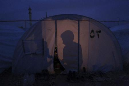 Shadows of Syrian refugees in a tent are seen at Bab al-Salam refugee camp in Azaz