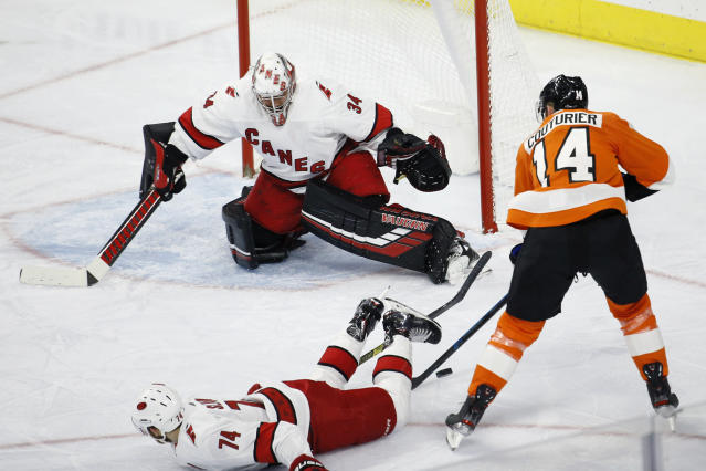 Philadelphia Flyers' Sean Couturier (14) cannot get a shot past Carolina Hurricanes' Petr Mrazek (34) and Jaccob Slavin (74) during the second period of an NHL hockey game, Tuesday, Nov. 5, 2019, in Philadelphia. (AP Photo/Matt Slocum)
