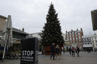 People wearing face masks walk past a Christmas tree in Covent Garden, during England's second coronavirus lockdown in London, Thursday, Nov. 26, 2020. Most people in England will continue to face tight restrictions on socializing and business after a nationwide lockdown ends next week, the government announced Thursday. (AP Photo/Matt Dunham)