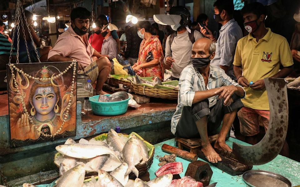A vendor waits for customers inside a crowded fish market, after authorities eased lockdown restrictions - Reuters