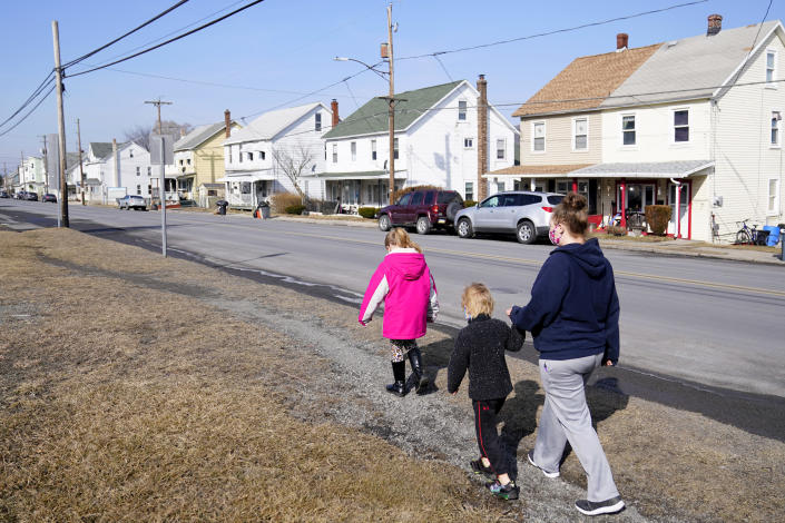From right, Melissa Weirich, walks with her son, Julien Heim, 4, and daughter, Kacie Thompson, 9, to visit the former home of Kacie's friend, Ava Lerairo, Thursday, March 11, 2021, in Lansford, Pa. On May 26, 2020, Ava; her mother, Ashley Belson, and Ava's father, Marc Lerario were found fatally shot. (AP Photo/Matt Slocum)