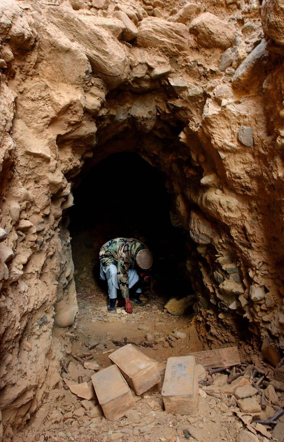 """<div class=""""inline-image__caption""""><p>A mujahadeen soldier picks up an item at the entrance to a former Al-Qaeda cave December 24, 2001 in Tora Bora, Afghanistan. </p></div> <div class=""""inline-image__credit"""">Chris Hondros/Getty</div>"""
