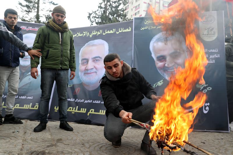 A Palestinian man burns representations of U.S. flag and Israeli flag in front of posters of Iranian Major-General Qassem Soleimani during a protest in Gaza