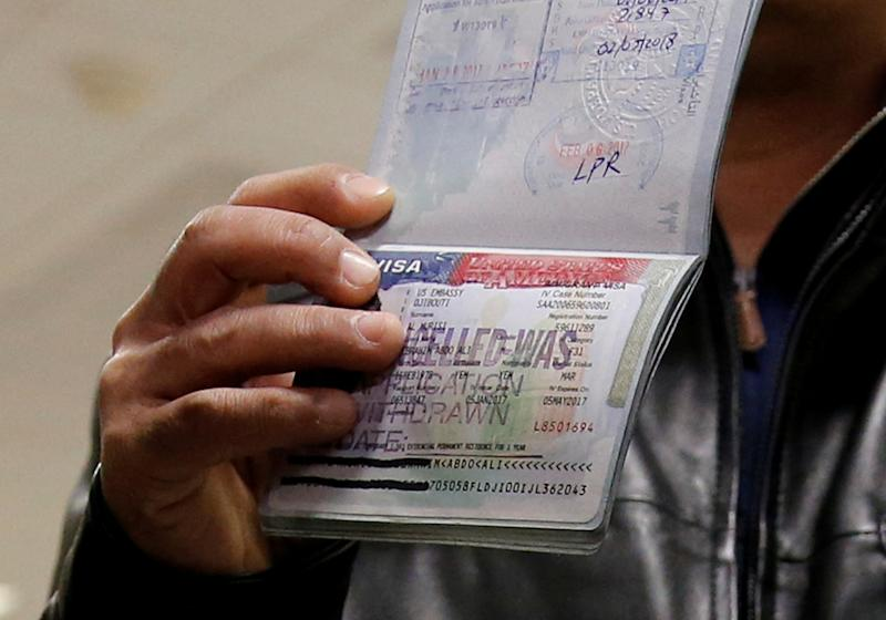 FILE PHOTO - A member of the Al Murisi family, Yemeni nationals who were denied entry into the U.S. last week because of the recent travel ban, shows the cancelled visa in their passport in Chantilly