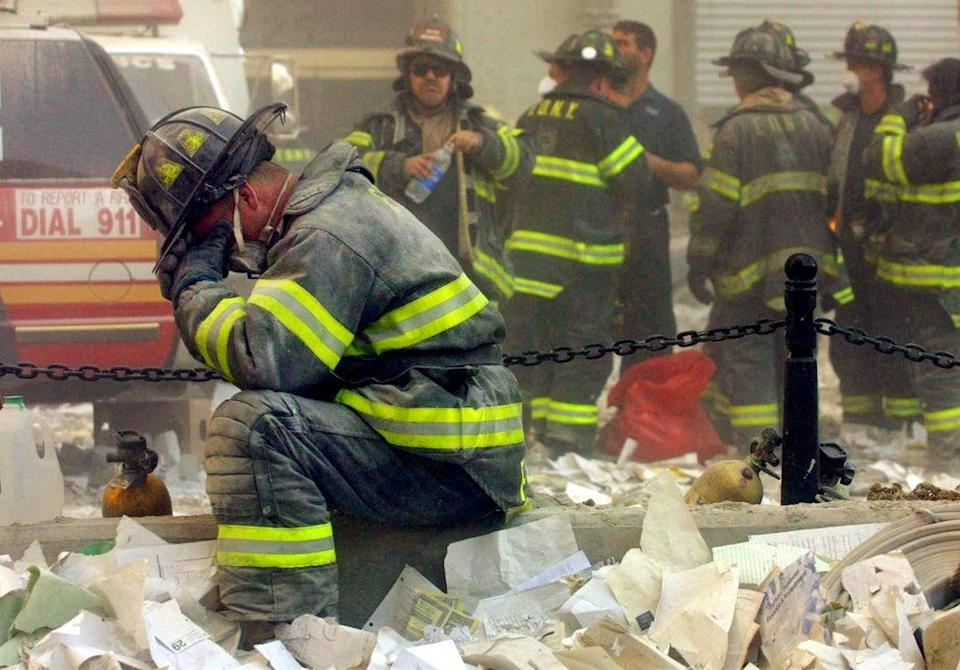 Firefighter Gerard McGibbon, of Engine 283 in Brownsville, Brooklyn, prays after the buildings collapsed (Getty)