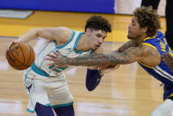 Charlotte Hornets guard LaMelo Ball, left, is defended by Golden State Warriors guard Kelly Oubre Jr. during the first half of an NBA basketball game in San Francisco, Friday, Feb. 26, 2021. (AP Photo/Jeff Chiu)