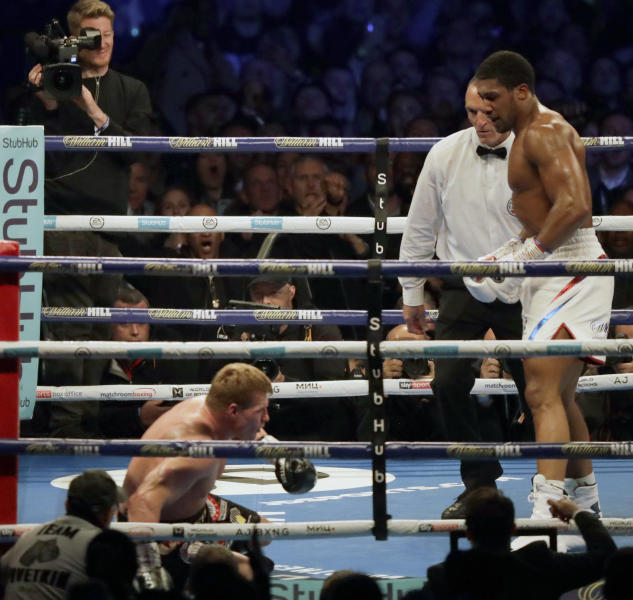 Russian boxer Alexander Povetkin goes down after taking a punch from British boxer Anthony Joshua, right, in their WBA, IBF, WBO and IBO heavyweight titles fight at Wembley Stadium in London, Saturday, Sept. 22, 2018. (AP Photo/Matt Dunham)
