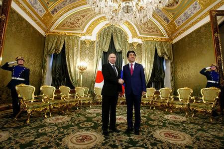 Russian President Putin shakes hands with Japanese PM Abe during meeting at Kremlin in Moscow