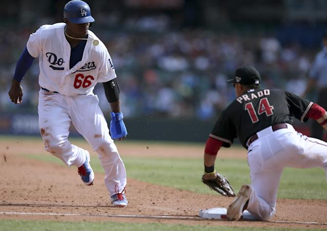 Los Angeles Dodgers' Yasiel Puig, left, is about to be tagged out at third base by the Diamondbacks' Marin Prado during the second game of the two-game Major League Baseball opening series between the Los Angeles Dodgers and Arizona Diamondbacks at the Sydney Cricket ground in Sydney, Sunday, March 23, 2014. (AP Photo/Rick Rycroft)