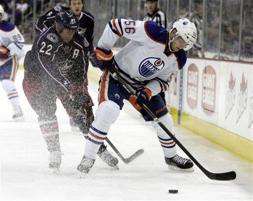 Edmonton Oilers' Teemu Hartikainen, right, of Finland, and Columbus Blue Jackets' Vinny Prospal, of the Czech Republic, work for the puck in the first period of an NHL hockey game, Sunday, March 25, 2012, in Columbus, Ohio. (AP Photo/Paul Vernon)