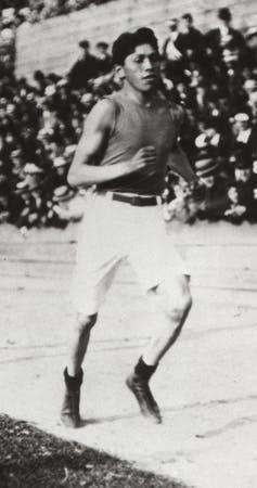 A black and white photograph of runner Tom Longboat on the track