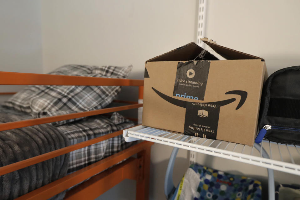An Amazon delivery box sits on a shelf of the room of Connie Wade, Wednesday, June 17, 2020, at Mary's Place, a family homeless shelter located inside an Amazon corporate building on the tech giant's Seattle campus. The facility is home to the Popsicle Place shelter program, an initiative to address the needs of homeless children with life-threatening health conditions. (AP Photo/Ted S. Warren)